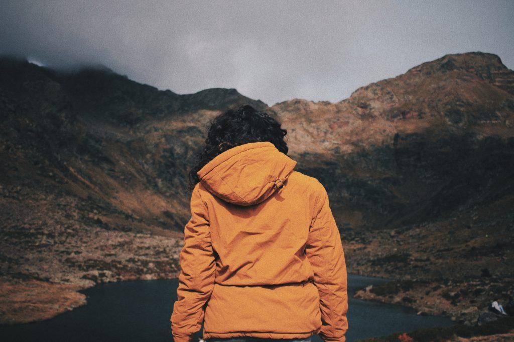 Mujer contemplando el paisaje de montaña frente a un lago